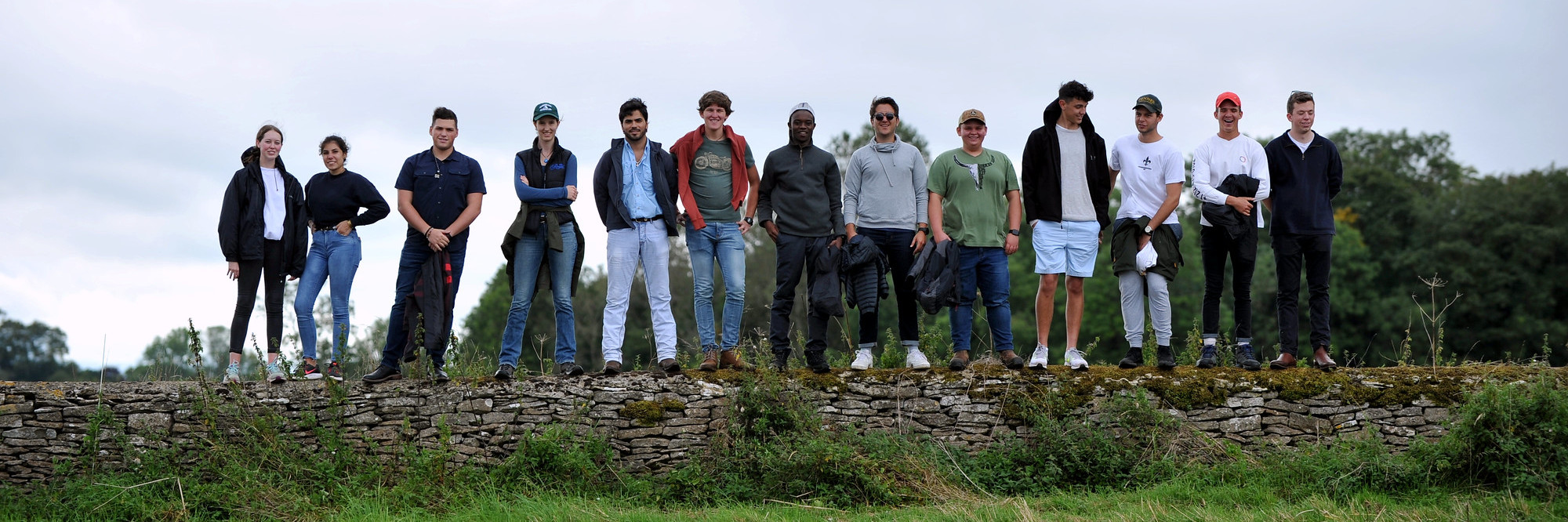 A group of thirteen students stood along a grey dry stone wall